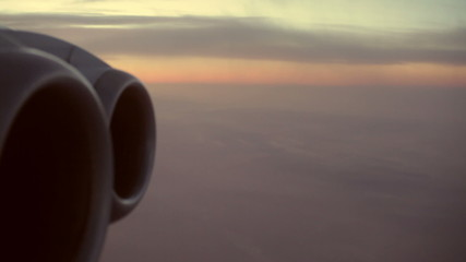 Detail of an aircraft engine flying in the morning sky.