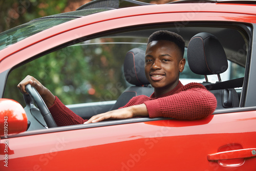 Male Teenage Driver Looking Out Of Car Window - 81392943