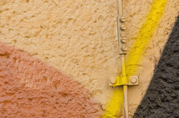 closeup of a wire mounted to a textured wall with graffiti