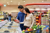 young couple shopping in a supermarket - 81394589