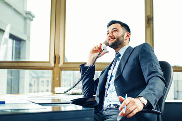 Young businessman talking on the phone at the office