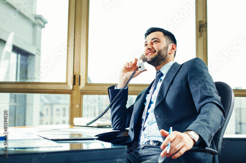 Leinwanddruck Bild Young businessman talking on the phone at the office