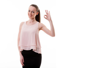 Smiling beautiful young woman showing ok sign or copyspace for