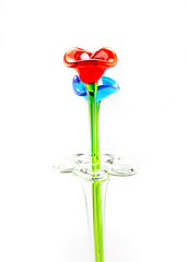 Flower made of glass in red and blue color in vase on white back