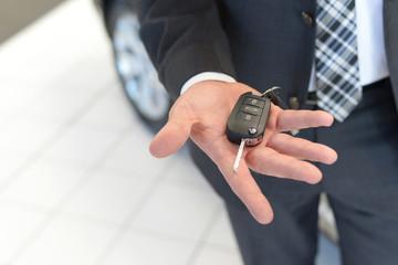 Verkäufer hält neuen Autoschlüssel in der Hand