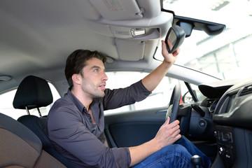 Mann schaut sich PKW in einem Autohaus an
