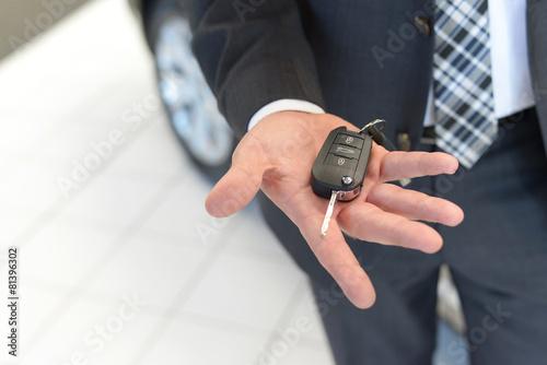 Leinwandbild Motiv Verkäufer hält neuen Autoschlüssel in der Hand