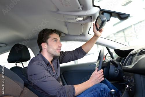 Leinwanddruck Bild Mann schaut sich PKW in einem Autohaus an