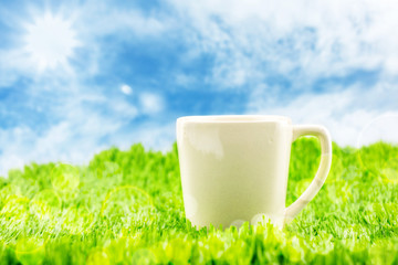 White coffee cup on green grass with blue sky and sunburst with