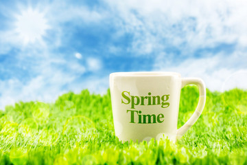 White coffee cup with spring time word on green grass with blue