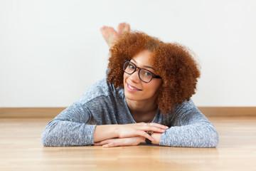 Black African American teenage girl lying down on the wood floor