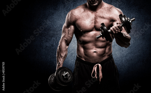 Closeup of a muscular young man lifting weights on dark backgrou - 81397101