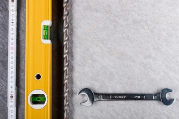 Wasserwaage Zollstock Bohrer Schraubenschlüssel auf Steinplatten