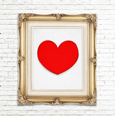 Red heart icon in golden vintage photo frame on white brick wall