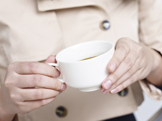 close-up of female's hands holding a cup of coffee