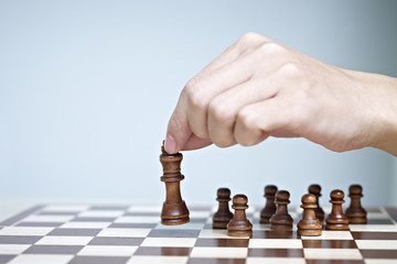 close-up of a man's hand moving a chess piece