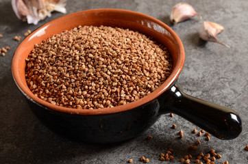 Buckwheat in a bowl with garlic on a stone background