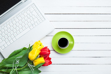 Cup of coffee and tulips with notebook