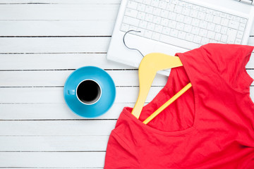 Cup of coffee and hanger with red dress near computer