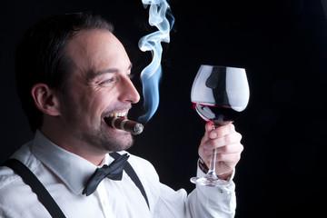 Mann mit Rotwein und Zigarre lebt ungesund aber glücklich
