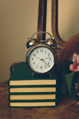 Clock with books and flowers in vintage color