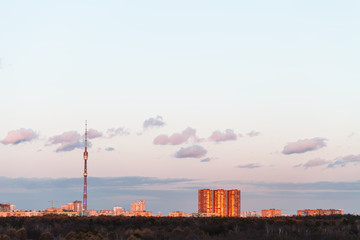 TV tower and urban buildings in spring sunset