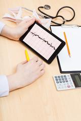 physician checks patient electrocardiogram