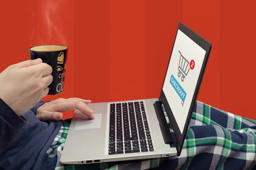 Man using a laptop and drinking coffee while resting on couch. O