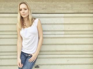 Blondes Mädchen lehnt an Wand
