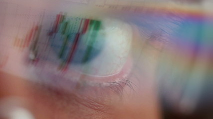 Closeup of glasses wearing men looking into a monitor.