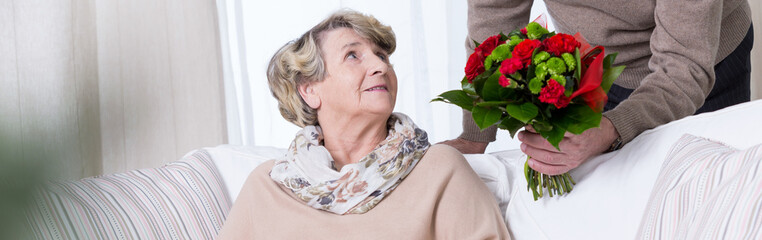 Senior woman getting anniversary bouquet
