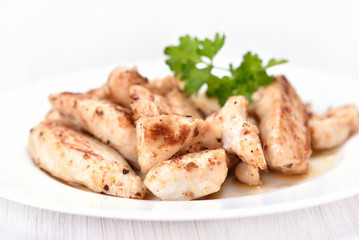 Toasted chicken meat sliced on white plate