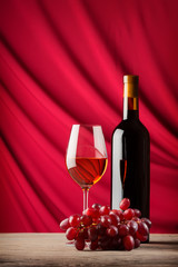 Bottle and glass of red wine on a background of scarlet satin