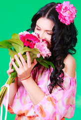 Spring portrait of a pretty young brunette smelling flowers