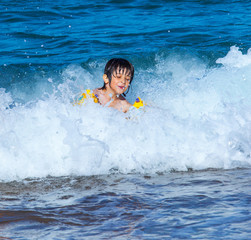 Little boy laughing in the foam of waves at sea