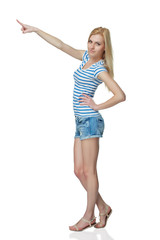 Happy young denim girl in shorts standing casually in full lengt