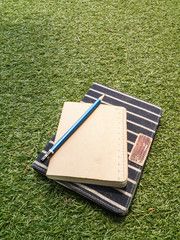 Notebook  and pencil on green grass background