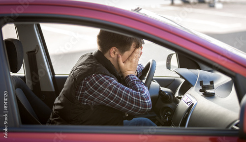 Leinwanddruck Bild portrait of shocked male driver closing face with hands