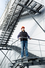 construction worker standing on steel staircase at factory
