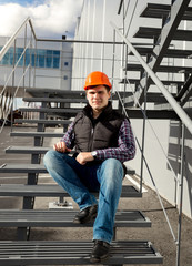 smiling worker relaxing on metal staircase during break