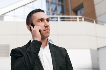 Young man in black suit talking on mobile phone looking away.