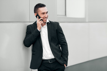 Smiling happy man talking on mobile phone in a black suit
