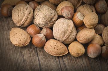 walnuts, almonds and peanuts on wooden background
