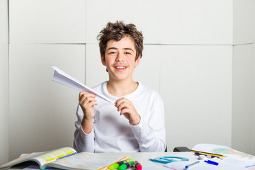 Caucasian boy playing with a paper airplane sitting in front of