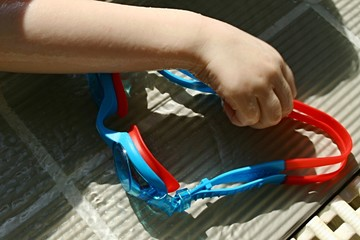 Child hand taking swim goggles from pool grating
