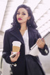 Bust young business woman holding coffee