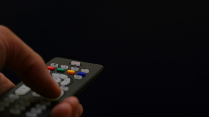 Watching TV-changing channels, blurred TV.