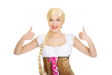 Woman in Bavarian dress with thumbs up.
