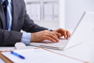 Businessman sitting in office, working with laptop computer