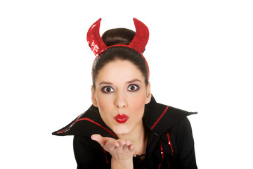 Woman in devil costume blowing a kiss.